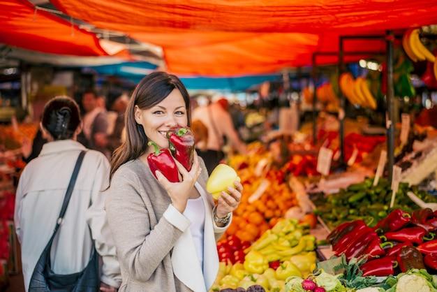 Image d'une belle femme achetant du paprika. profitant de l'odeur fraîche des légumes.