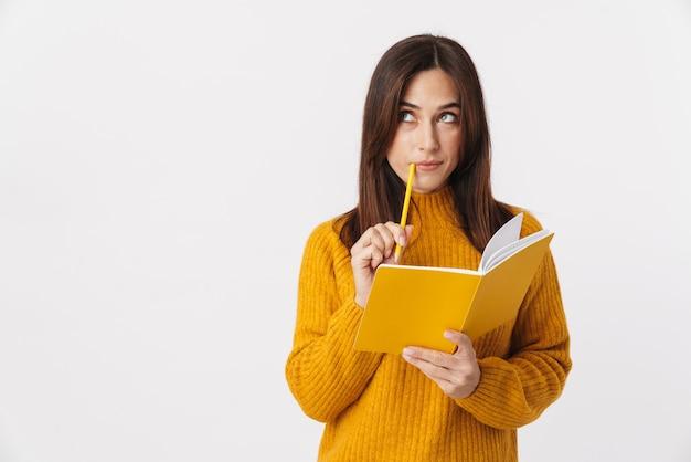 Image d'une belle femme adulte brune portant un chandail pensant et prenant des notes dans un livre de journal isolé sur blanc