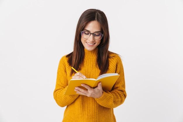 Image d'une belle femme adulte brune portant des lunettes souriant et prenant des notes dans un livre de journal isolé sur blanc
