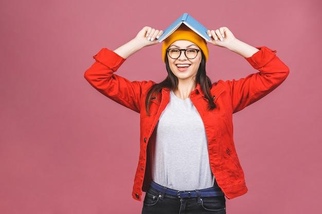 Image de belle femme adulte brune portant des lunettes en souriant et tenant un livre à sa tête