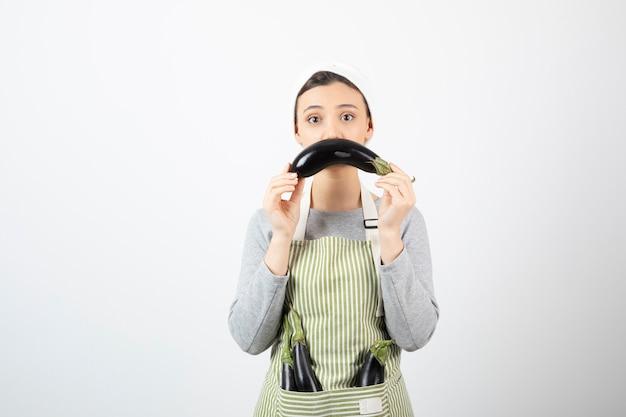 Image d'une belle femme au foyer ayant des aubergines en tablier et en montrant une