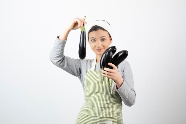 Image de belle femme au foyer en tablier montrant des aubergines fraîches