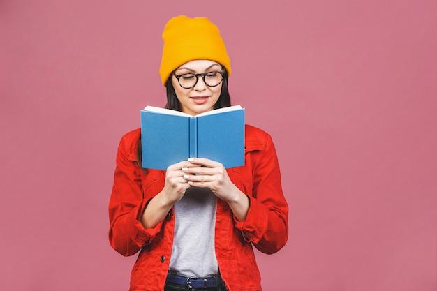 Image de belle femme brune adulte portant des lunettes en souriant et en lisant le livre