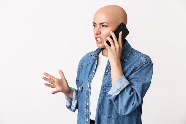 Image d'une belle femme chauve en colère mécontente posant isolée, parlant par téléphone portable.