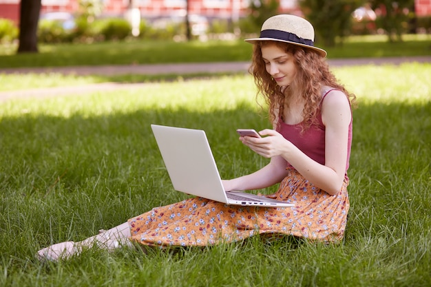 Image de belle femme élégante au chapeau, assis sur l'herbe verte avec un ordinateur portable et un téléphone dans les mains, a des cours en ligne, travaillant en plein air, utilisant internet sans fil. concept de pigiste et de style de vie.