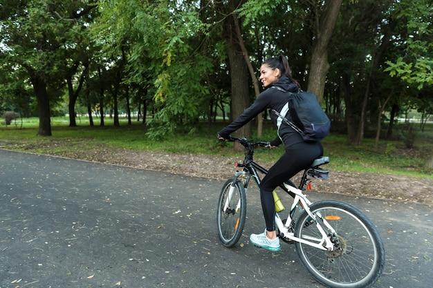 Image d'une belle femme marchant à vélo dans le parc à l'extérieur.