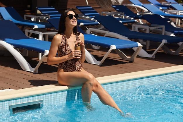 Image de belle femme se détendre dans la piscine. femme, à, peau bronzée saine, magnifique, femme, apprécier, heure d'été, à, luxe, recours