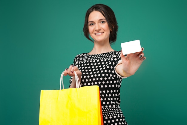 Image de belle femme en vêtements mouchetés, debout avec achats et en coupe dans les mains