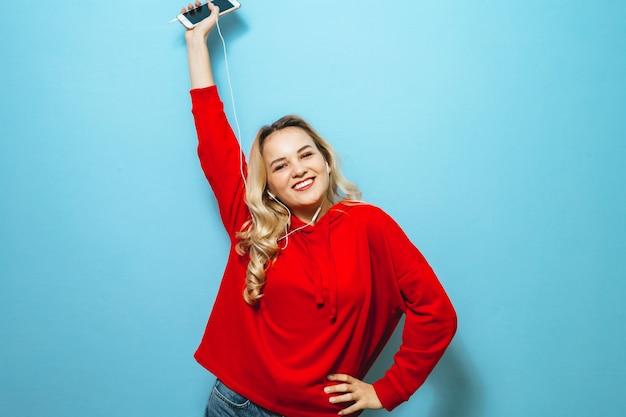 Image d'une belle fille blonde excitée, écouter de la musique dans les écouteurs et danser sur le mur bleu
