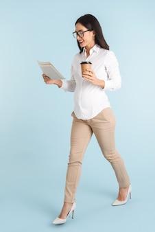 Image d'une belle jeune femme d'affaires isolée lecture journal de boire du café.