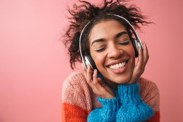 Image de la belle jeune femme africaine émotionnelle posant isolé musique d'écoute avec des écouteurs