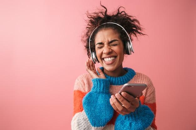 Image de la belle jeune femme africaine émotionnelle posant de la musique d'écoute isolée avec des écouteurs à l'aide de téléphone mobile.
