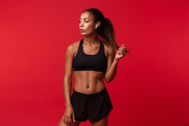 Image d'une belle jeune femme africaine de remise en forme sportive posant isolée sur un mur rouge à l'écoute de la musique avec des écouteurs.