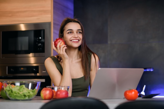 Image d'une belle jeune femme avec apple assis à l'intérieur à l'aide d'un ordinateur portable.
