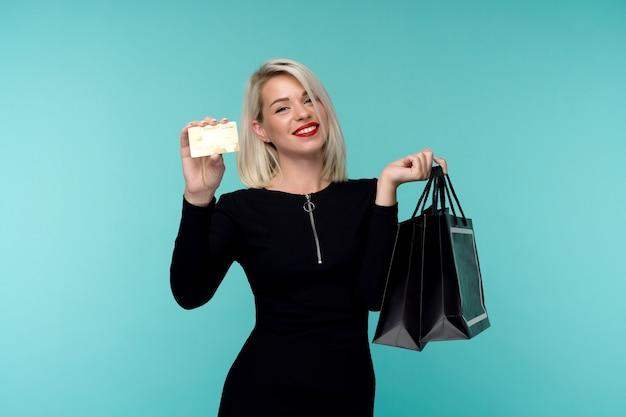 Image d'une belle jeune femme blonde heureuse posant isolé sur fond de mur bleu tenant des sacs à provisions. concept de vacances vendredi noir. vente