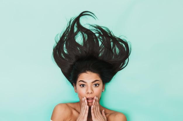Image de la belle jeune femme choquée se trouve isolée sur la lumière bleue. concept de cheveux sains.
