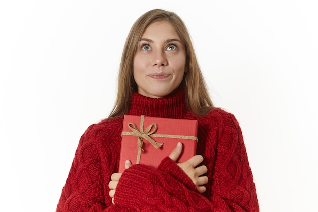 Image de la belle jeune femme européenne ravie en pull marron embrassant présent inconnu et levant avec une expression faciale joyeuse rêveuse, essayant de deviner ce qui est à l'intérieur de la boîte de papier rouge