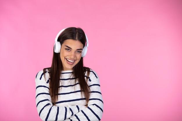 Image d'une belle jeune femme heureuse assez excitée posant isolé sur mur rose