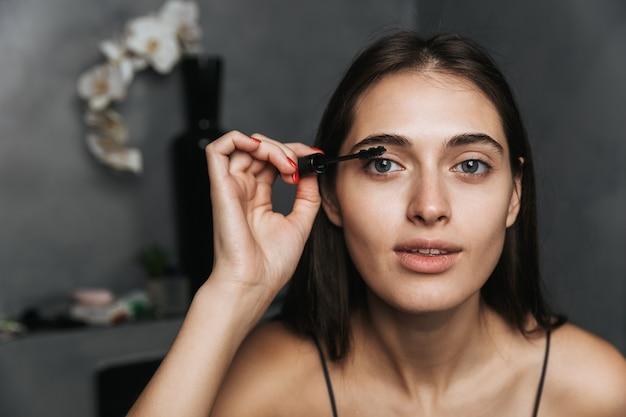 Image d'une belle jeune femme mignonne joyeuse dans la salle de bain prendre soin de sa peau en se maquillant avec du mascara de cils.