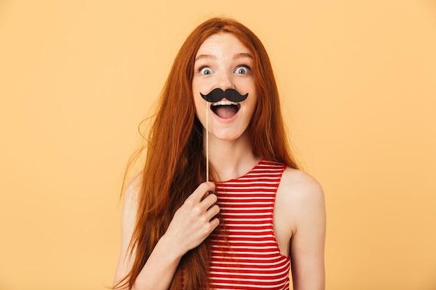 Image d'une belle jeune femme rousse émotionnelle choquée posant isolée sur un mur jaune tenant une fausse moustache.
