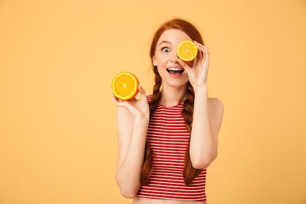 Image d'une belle jeune femme rousse heureuse et choquée posant isolée sur un mur jaune tenant un œil couvrant orange.