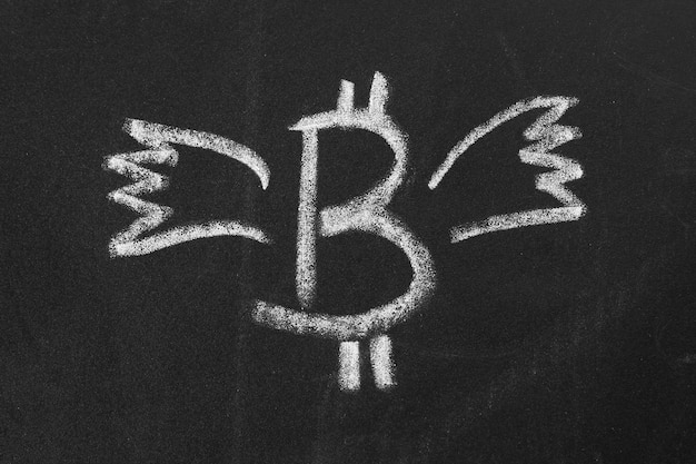 Image bitcoin avec des ailes de craie sur un tableau noir.