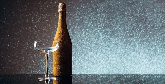 Image d'une bouteille de champagne dans un emballage d'or avec un verre de vin vide sur fond gris