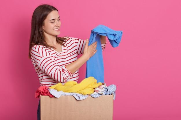 Image de brune séduisante dame regardant de côté, souriant sincèrement, mettant les vêtements donnés dans l'ordre, tenant un pantalon bleu dans les mains