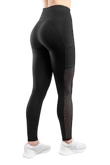 Image de cadre d'une figure féminine en tenue de sport noire serrée, fond blanc isolé. vue verticale.