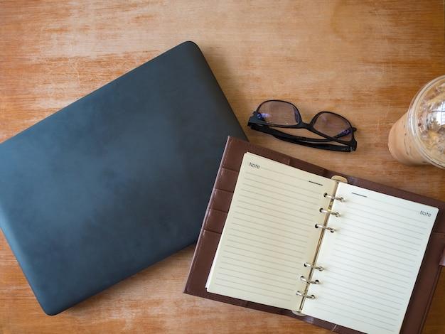 Image de cahier ouvert avec du café glace et des lunettes et un ordinateur portable sur une table en bois.