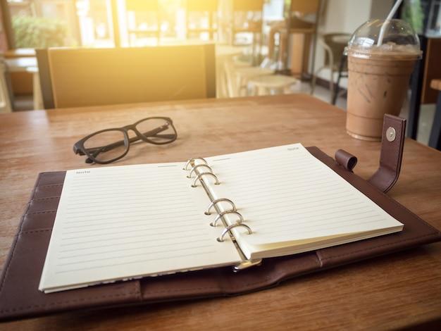 Image de cahier ouvert avec du café glacé et des verres sur une table en bois.