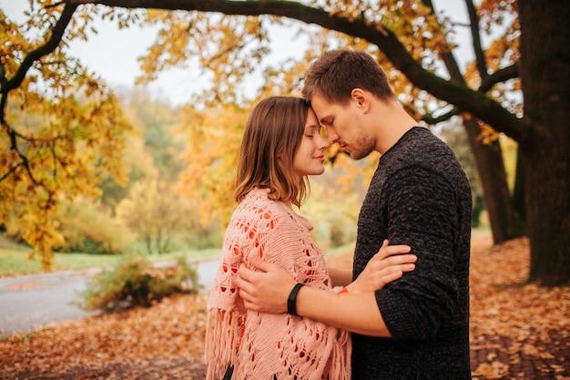 Image calme et paisible d'un couple penché l'un vers l'autre. ils gardent leurs fronts ensemble. le couple est dans le parc.