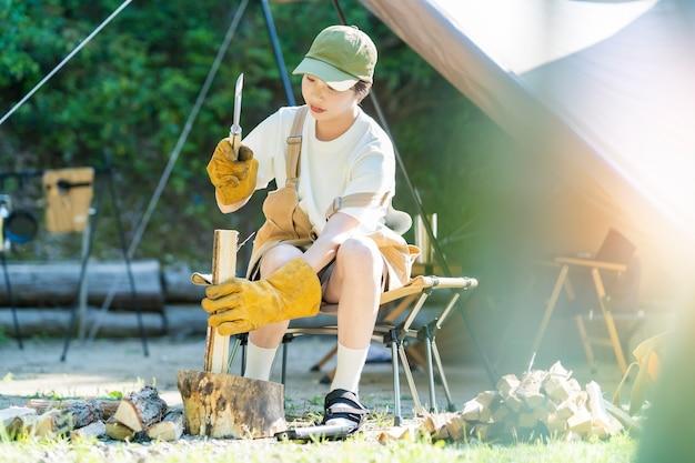 Image camp solo - jeune femme coupant du bois de chauffage