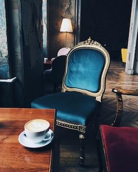 Image d'une chaise ancienne et d'une tasse de cappuccino ou d'espresso sur une table en bois dans une pièce négligée aux murs en ruine