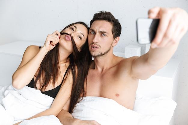 Image de charmant couple prenant selfie sur téléphone portable, allongé dans son lit à la maison ou dans un appartement d'hôtel