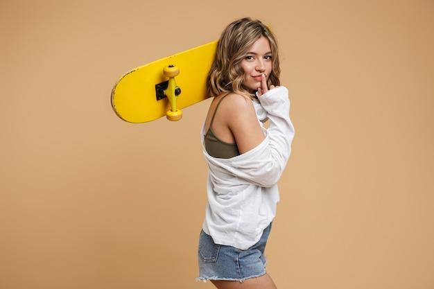 Image d'une charmante jeune femme portant un short en jean avec des écouteurs et une planche à roulettes isolée sur un mur beige