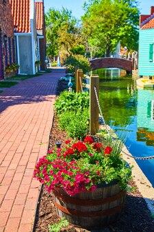 Image de chemin de brique dans le village néerlandais avec des pots de fleurs le long du canal d'eau