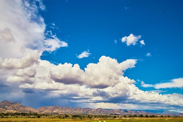 Image de ciel bleu ouvert avec des nuages d'orage entrant contre les montagnes du désert le long de l'horizon