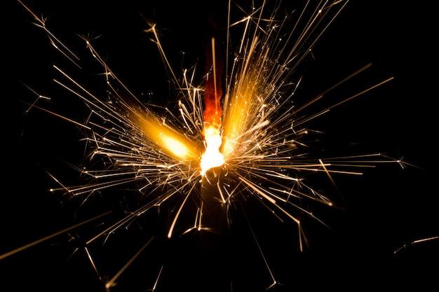 Image d'un cierge magique allumé tirant des étincelles dans la nuit