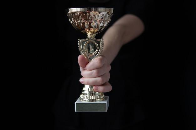 Image clé faible d'une femme tenant une coupe du trophée sur fond noir