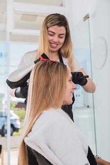 Image d'un coiffeur joyeux séchant les cheveux d'une belle jeune femme, travaillant dans son salon de beauté.