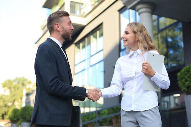 Image de collègues discutant de documents et serrant la main près du bureau.