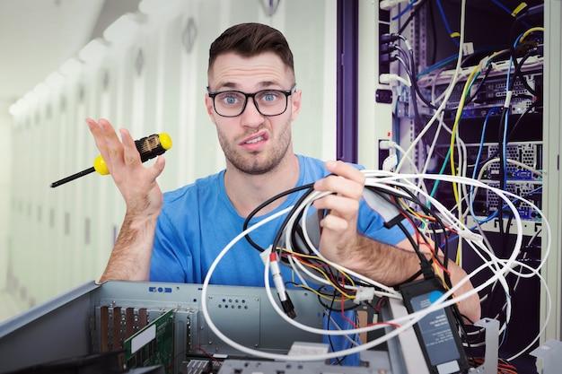 Image composite du portrait d'un professionnel confus avec un tournevis et des câbles en face de l'ope