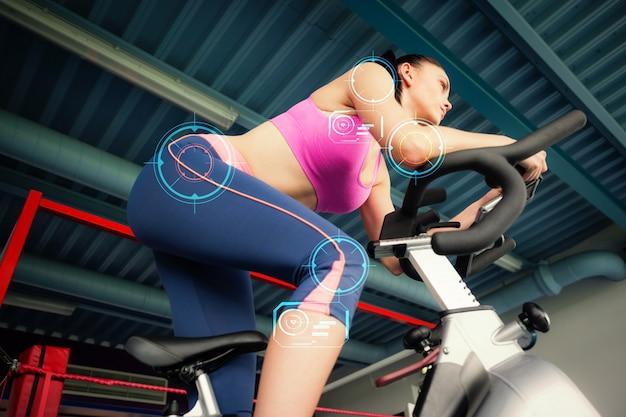 Image composite d'une jeune femme déterminée travaillant à la classe de spinning