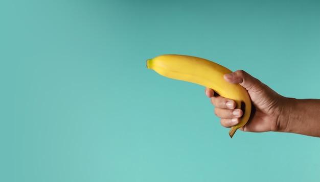 Image de concept de banane. main tenant une banane sur le fond bleu, ressemble à une arme à feu