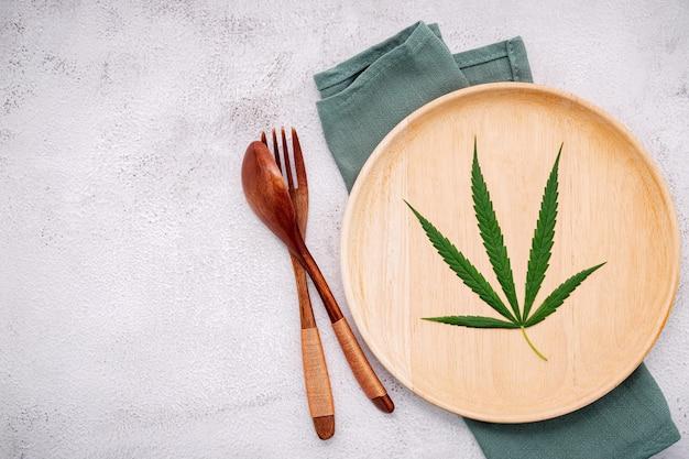 Image conceptuelle alimentaire d'une feuille de cannabis avec cuillère et fourchette sur béton blanc.