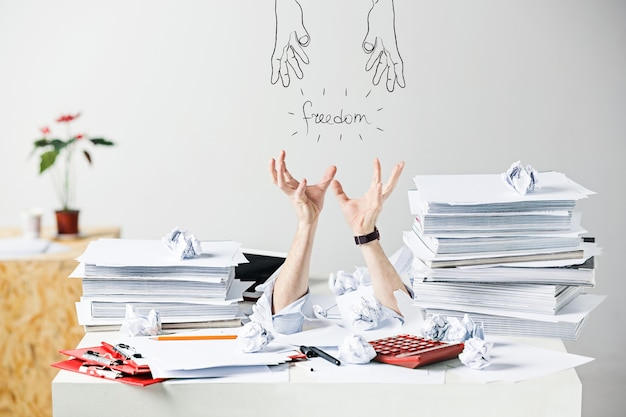 L'image conceptuelle ou le collage sur de nombreux papiers froissés sur le bureau du lieu de travail masculin stressé