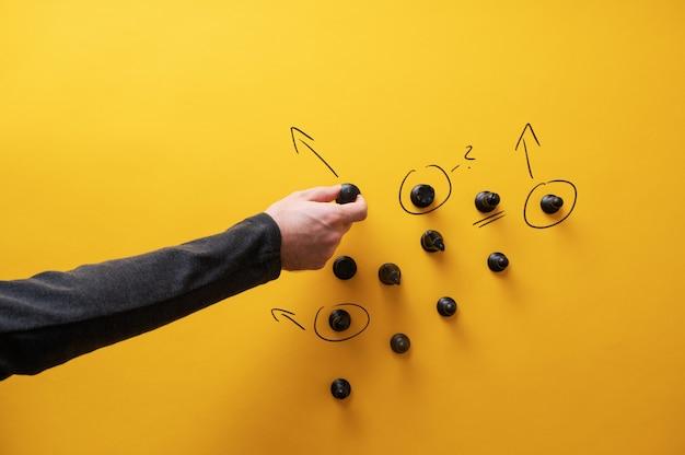 Image conceptuelle de la planification stratégique - main masculine dessinant des flèches et des points d'interrogation autour des figures d'échecs.