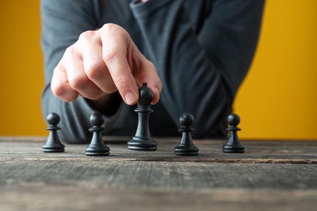 Image conceptuelle de la stratégie et de la puissance avec des pièces d'échecs de positionnement de main masculine sur planche de bois rustique.
