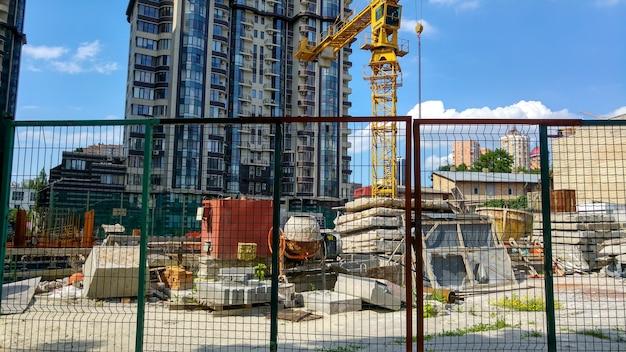 Image de la construction d'un bâtiment moderne derrière la clôture filaire à une belle journée ensoleillée
